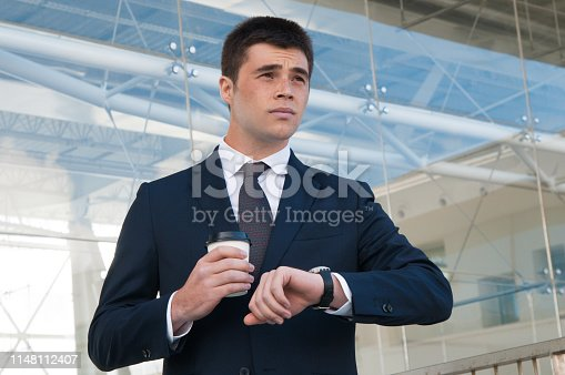 Pensive business man checking time on watch outdoors. Handsome guy holding plastic coffee cup and standing with building glass wall in background. Business appointment concept. Front view.