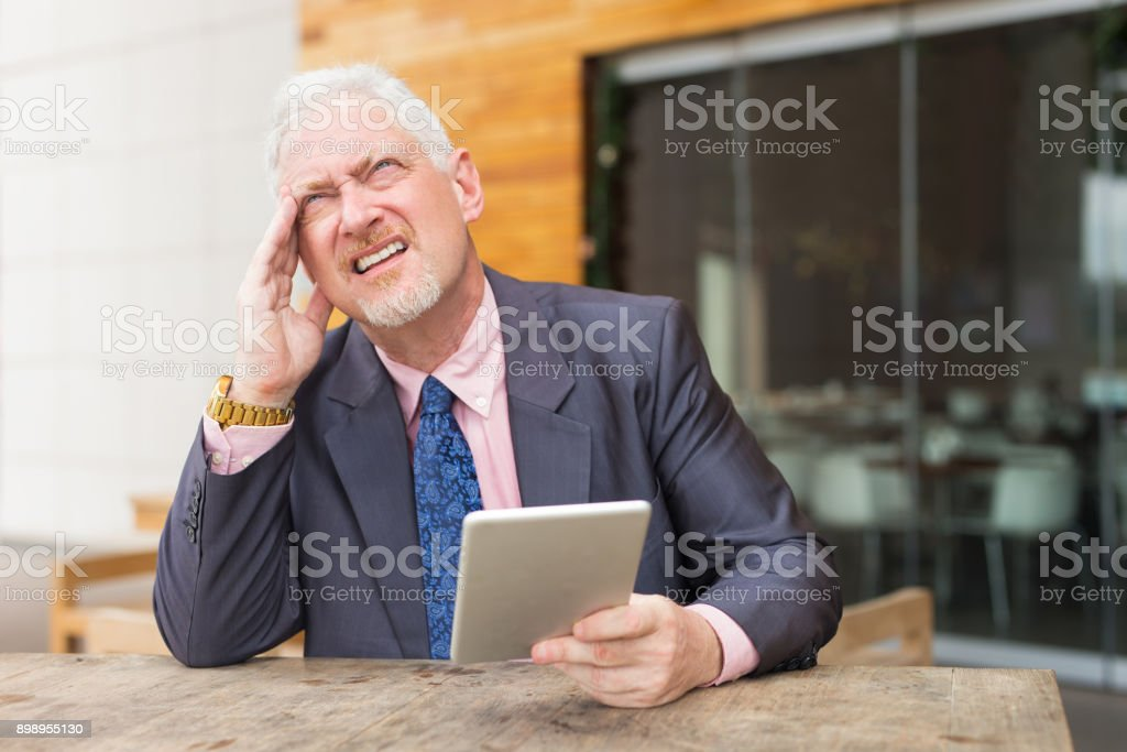 Pensive Business Man with Tablet in Street Cafe stock photo