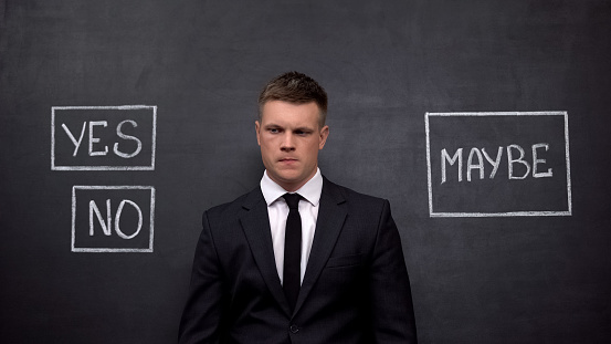 506662064 istock photo Pensive businessman doubting answer, yes no maybe buttons, solution search 1183376240