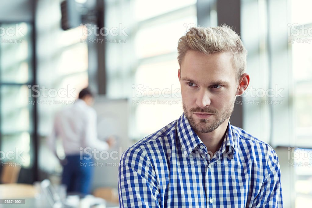 Pensive businessman in the office Portrait of confident businessman wearing shirt standing in the conference room. Coworker drawing on flipchart in the background. 2015 Stock Photo