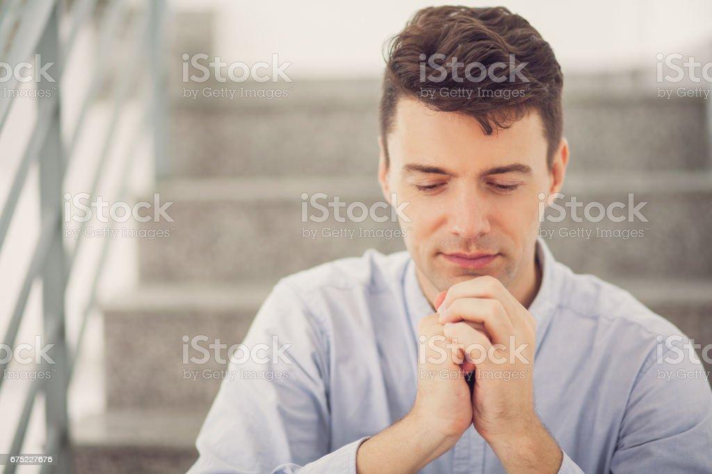 Pensive businessman praying on stairs_tone royalty-free stock photo