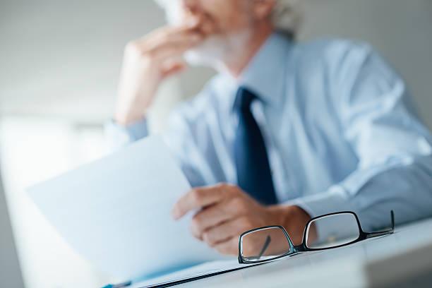 Pensif Homme d'affaires lire un contrat - Photo