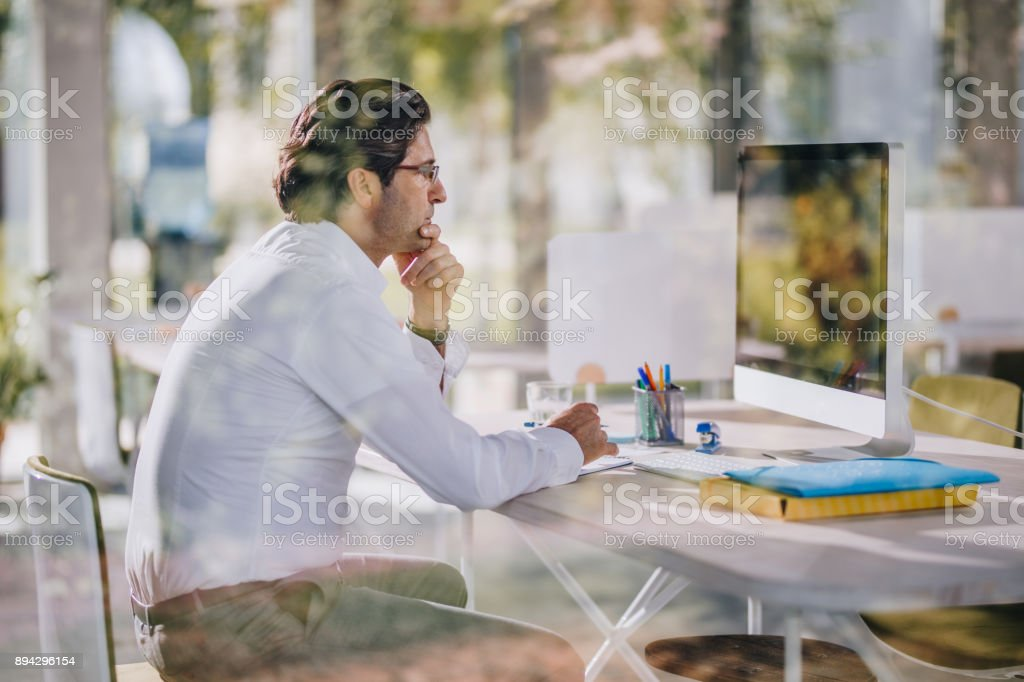 Pensive businessman reading an e-mail on desktop PC in the office. stock photo