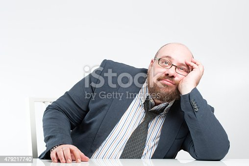 istock Pensive businessman sitting at the table. 479217740