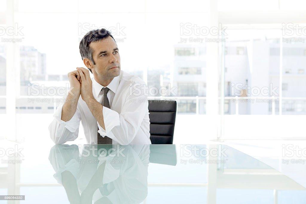 Pensive businessman sitting in board room stock photo