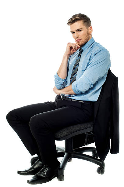 Pensive businessman sitting on the chair stock photo