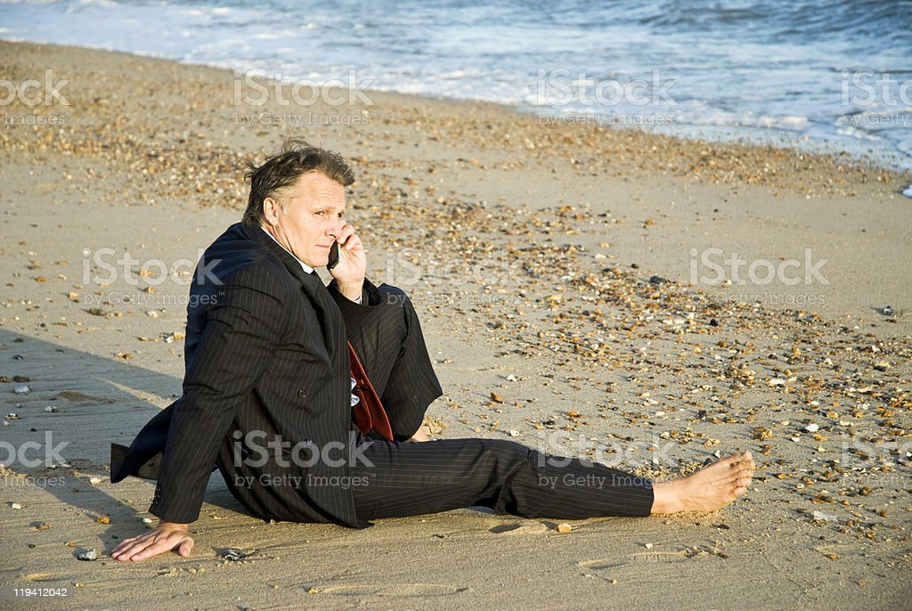 pensive businessman using cellphone on beach stock photo