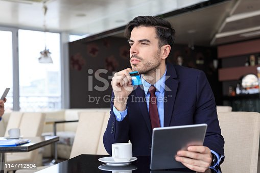 502723248 istock photo Pensive businessman using credit card and tablet in cafe 1147712804