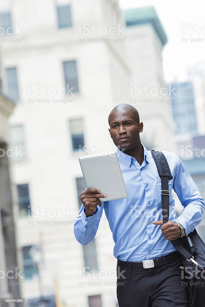 Pensive Businessman walking to work with tablet royalty-free stock photo