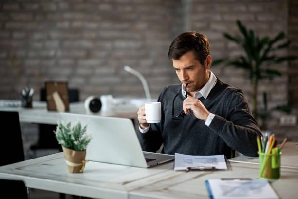 umfassender geschäftsmann, der auf laptop arbeitet, während er kaffee im büro trinkt. - einzelner mann über 30 stock-fotos und bilder