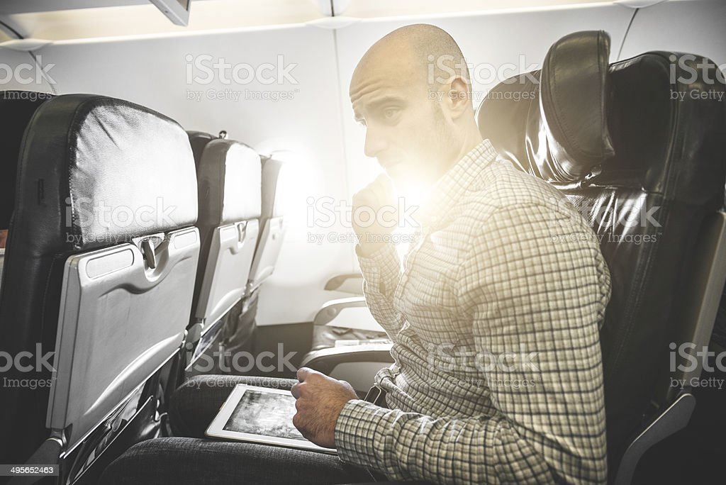 Pensive businessman working with digital tablet on the plane stock photo