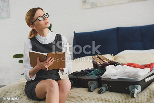 istock pensive businesswoman holding planner while packing suitcase on bed 947818984