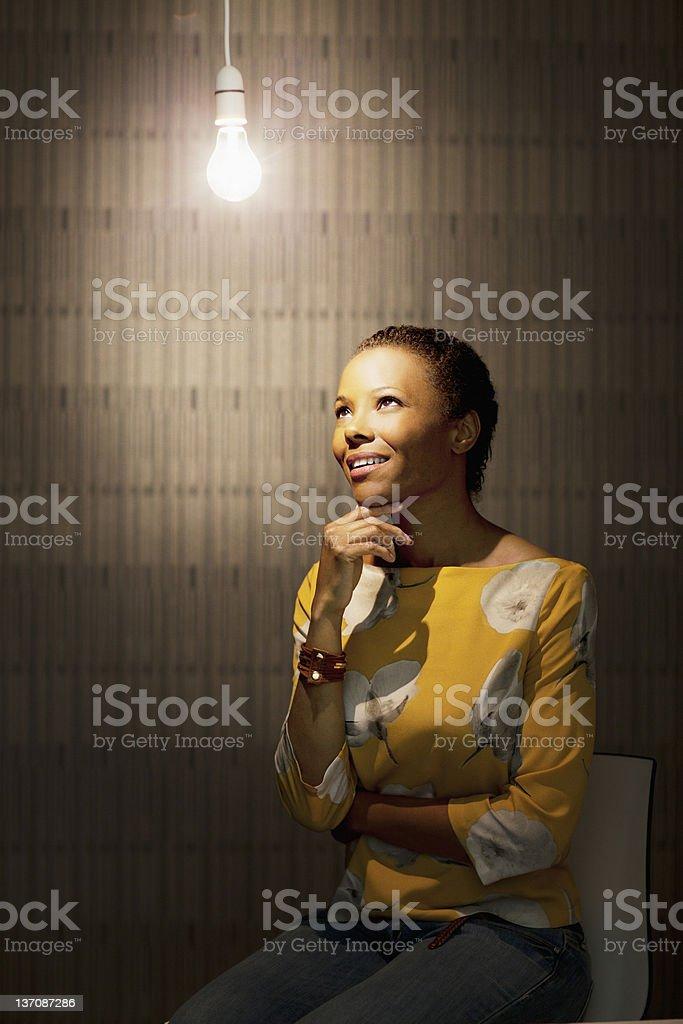 Pensive businesswoman sitting under illuminated light bulb royalty-free stock photo