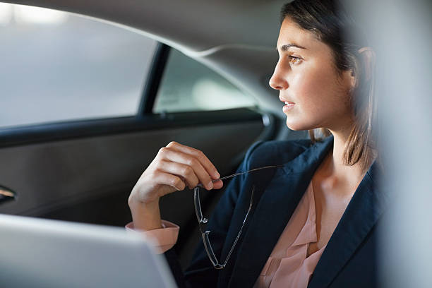 Pensive businesswoman with laptop in back seat of car stock photo