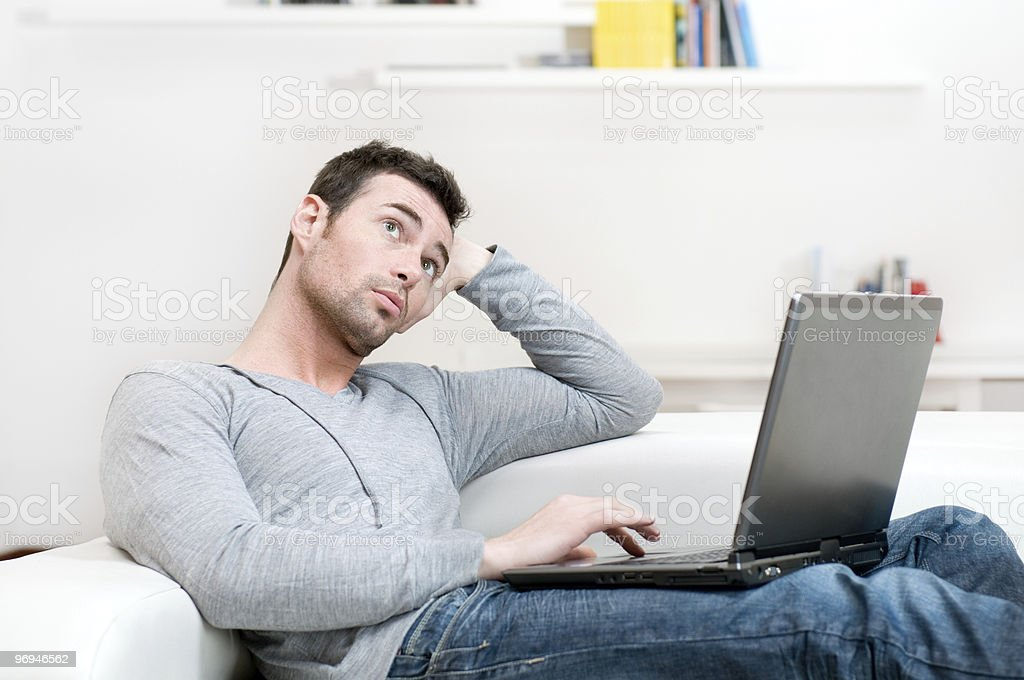 Pensive casual man working on laptop royalty-free stock photo