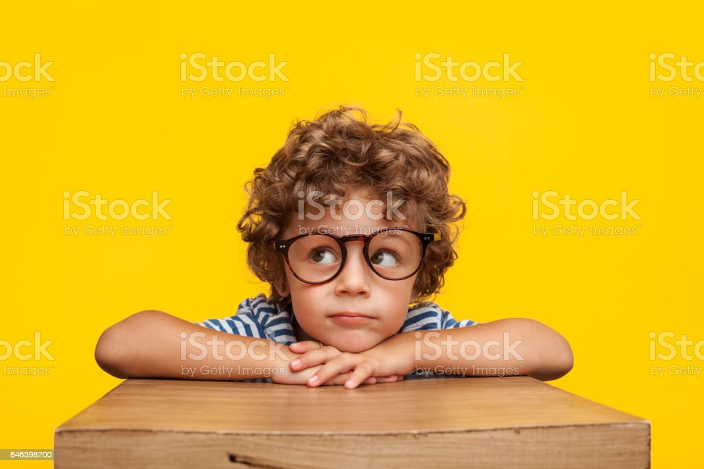 Pensive charming boy on studio background stock photo