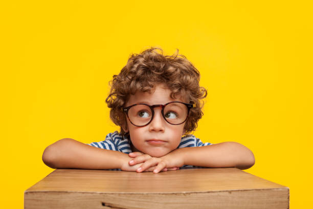 Pensive charming boy on studio background Portrait of curly boy in glasses leaning on box looking away pensively on orange background. schoolboy stock pictures, royalty-free photos & images
