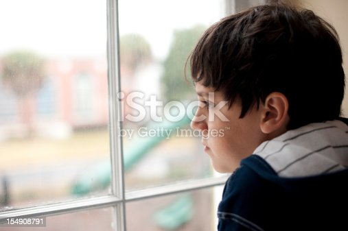 istock Pensive child looking through a window 154908791