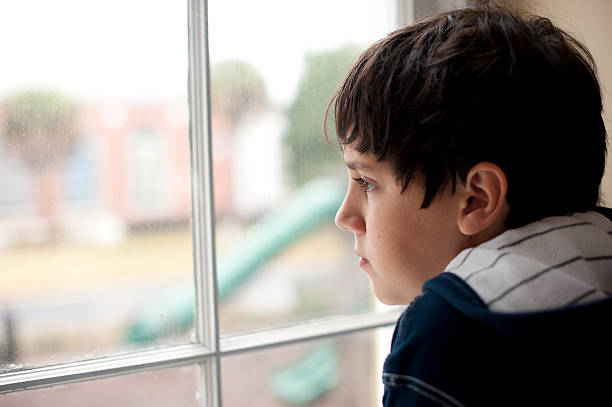 pensive child looking through a window - boy looking out window stock pictures, royalty-free photos & images
