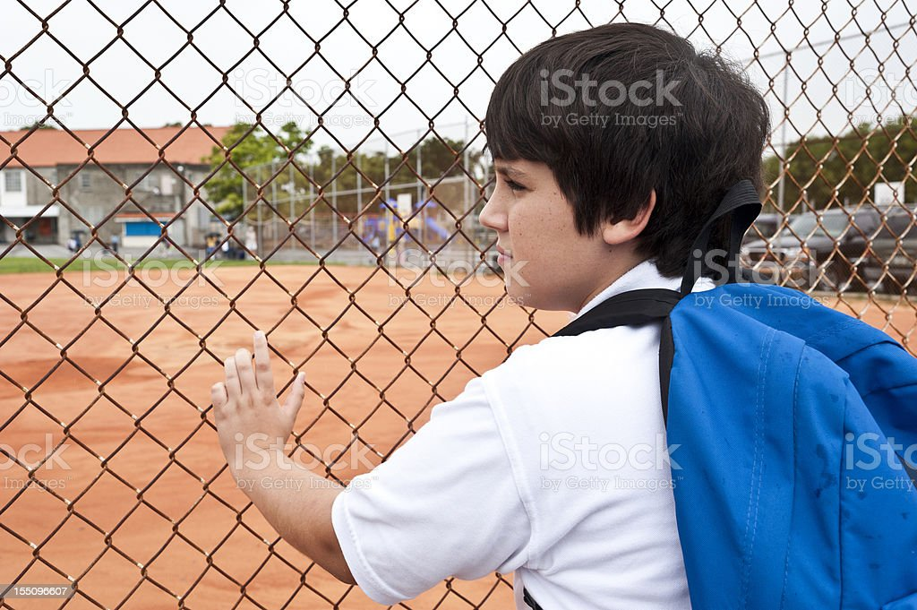 Pensive child looking through an school fence royalty-free stock photo