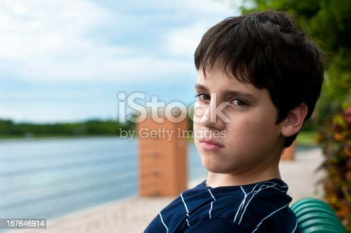 istock Pensive child sitting by the rive side 157646914