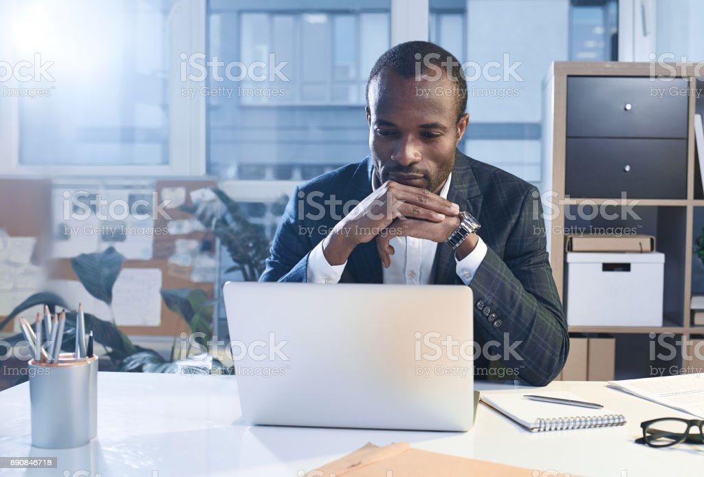 Pensive confident businessman is working on smart gadget Business project. Portrait of serious young elegant african man is sitting at table while putting elbow on desk and touching his chin. He is looking at screen of modern laptop thoughtfully. Copy space Businessman Stock Photo