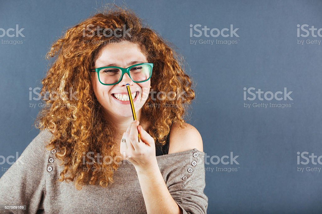 Pensive Curly Young Woman on Gray Background stock photo