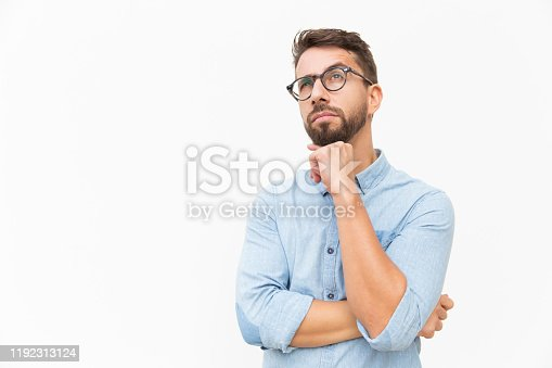 Pensive customer thinking over special offer, touching chin, looking up. Handsome young man in casual shirt and glasses standing isolated over white background. Advertising concept