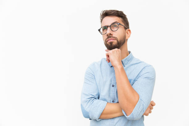 Pensive customer thinking over special offer Pensive customer thinking over special offer, touching chin, looking up. Handsome young man in casual shirt and glasses standing isolated over white background. Advertising concept reflection stock pictures, royalty-free photos & images