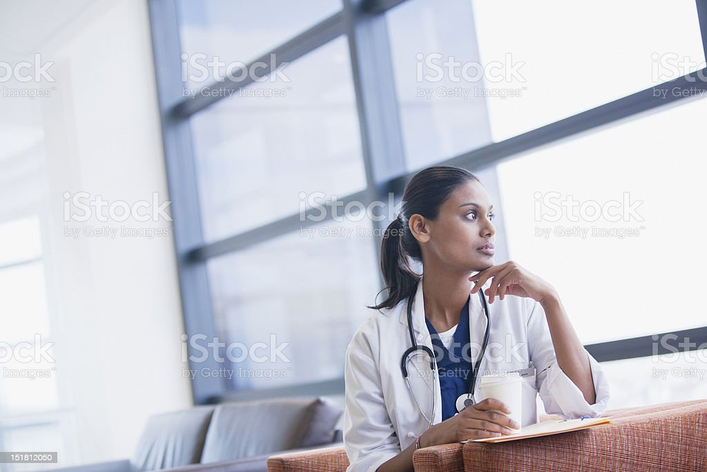 Pensive doctor drinking coffee and looking out window stock photo