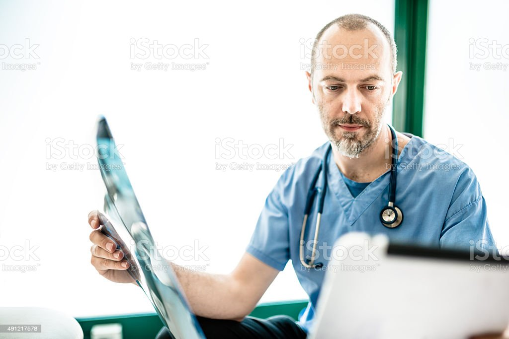 Pensive doctor looking the xray on the tablet stock photo