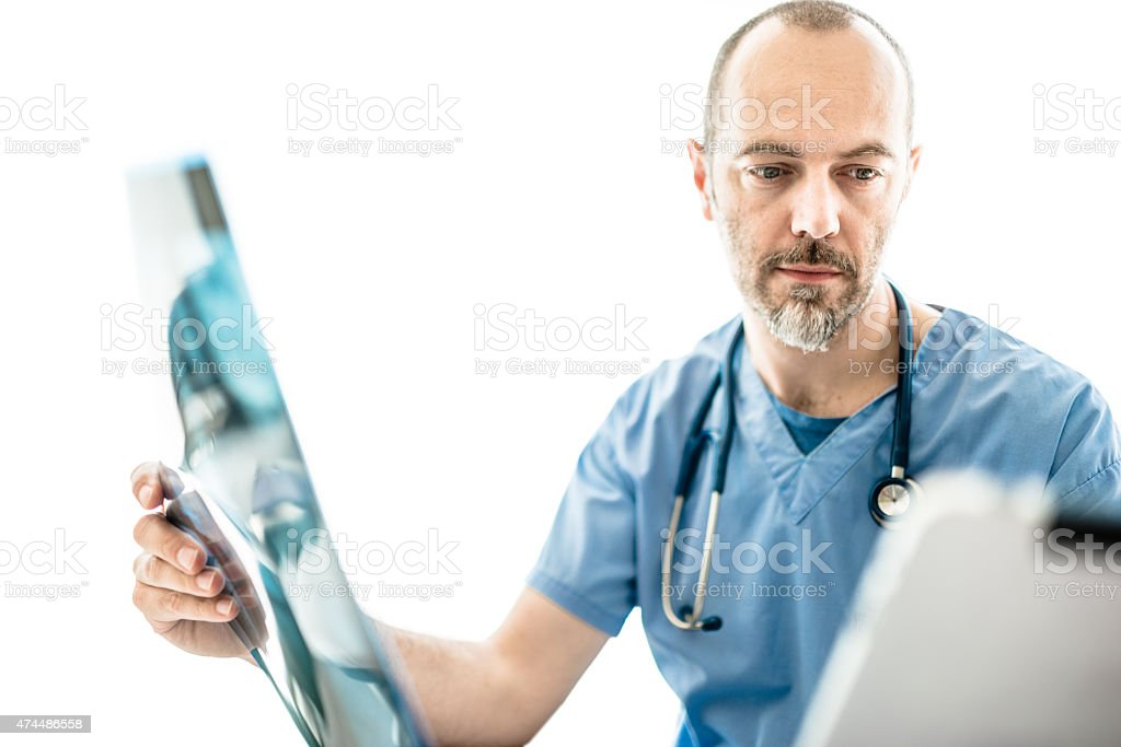 Pensive doctor looking the xray Pensive doctor looking the xray 2015 Stock Photo