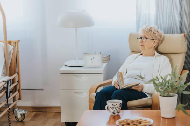 Pensive elderly lady sitting with a book in an armchair in a nursing home stock photo