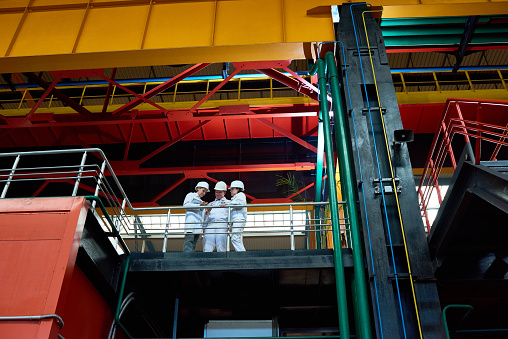 Below view of supervisors visiting modern factory to examine machines and equipments