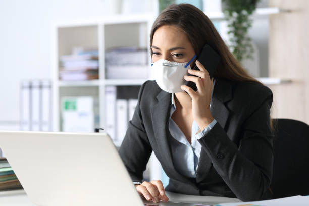 Pensive executive calling on phone avoiding coronavirus at office stock photo