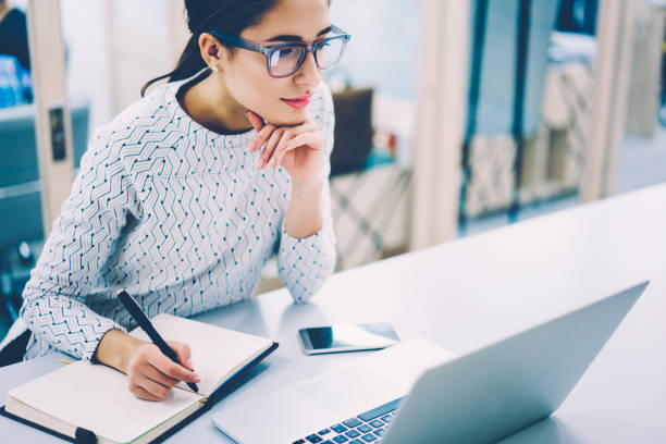 Pensive female administrative assistant checking report on laptop reading information and noting data,skilled woman watching online video online pondering on creating publication writing in notepad stock photo