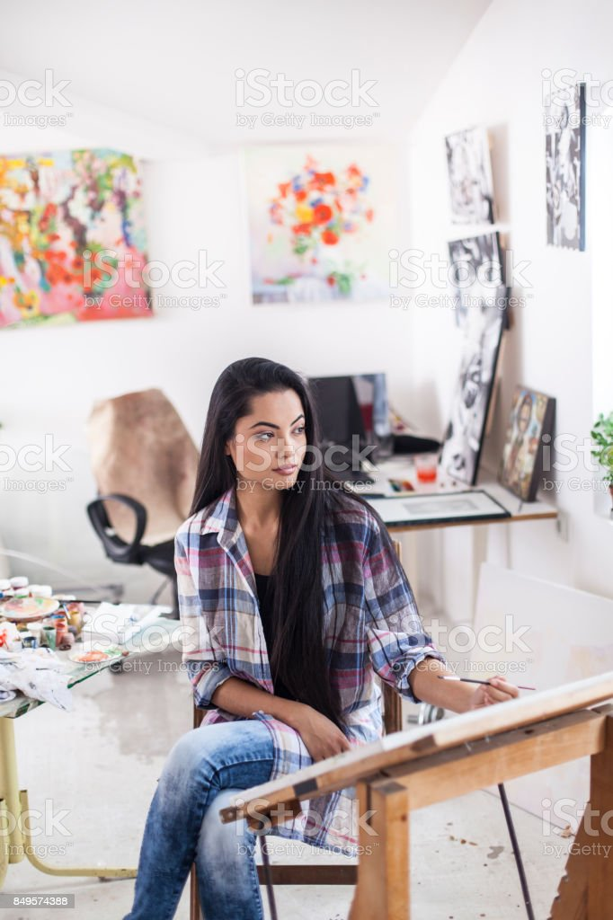 Pensive female artist in workshop stock photo