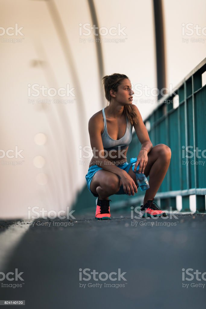 Pensive female athlete taking a break and crouching on the street. stock photo