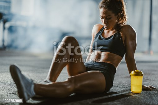 Young athletic woman resting on a water break in a gym.