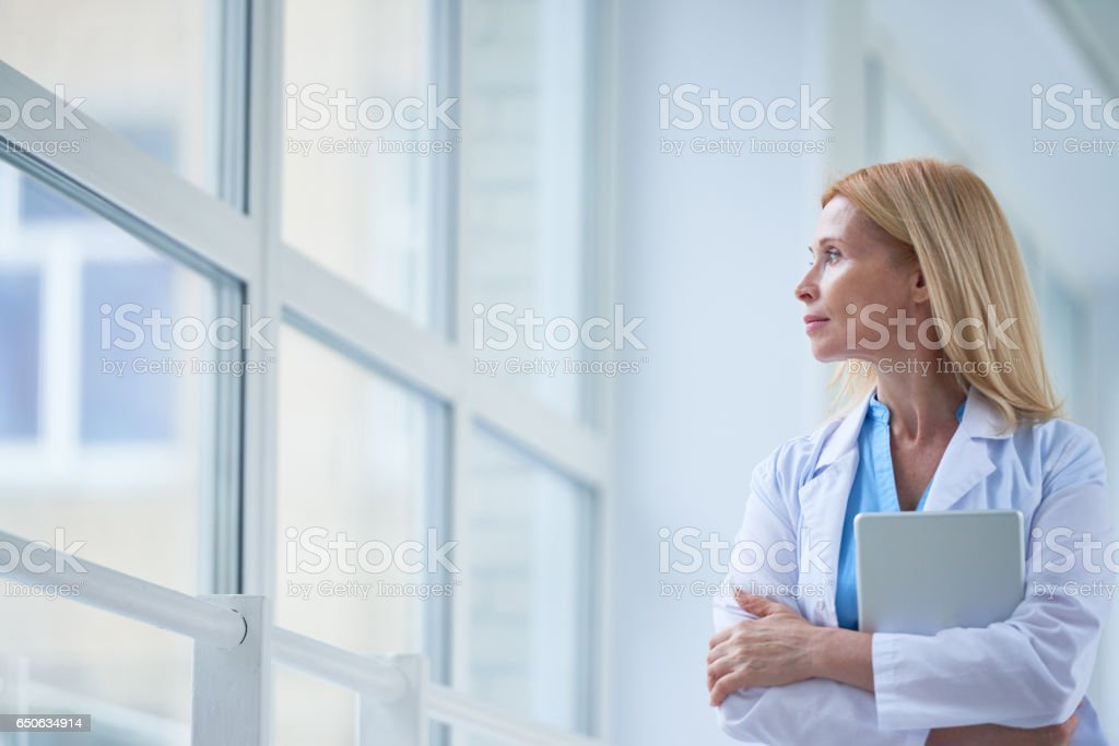 Pensive female doctor in corridor stock photo