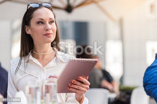 businesswoman expressing thoughtfulness while working with electronic tablet