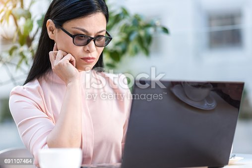 Business woman demonstrating thoughtfulness while looking at notebook computer. She locating at desk in cafeteria
