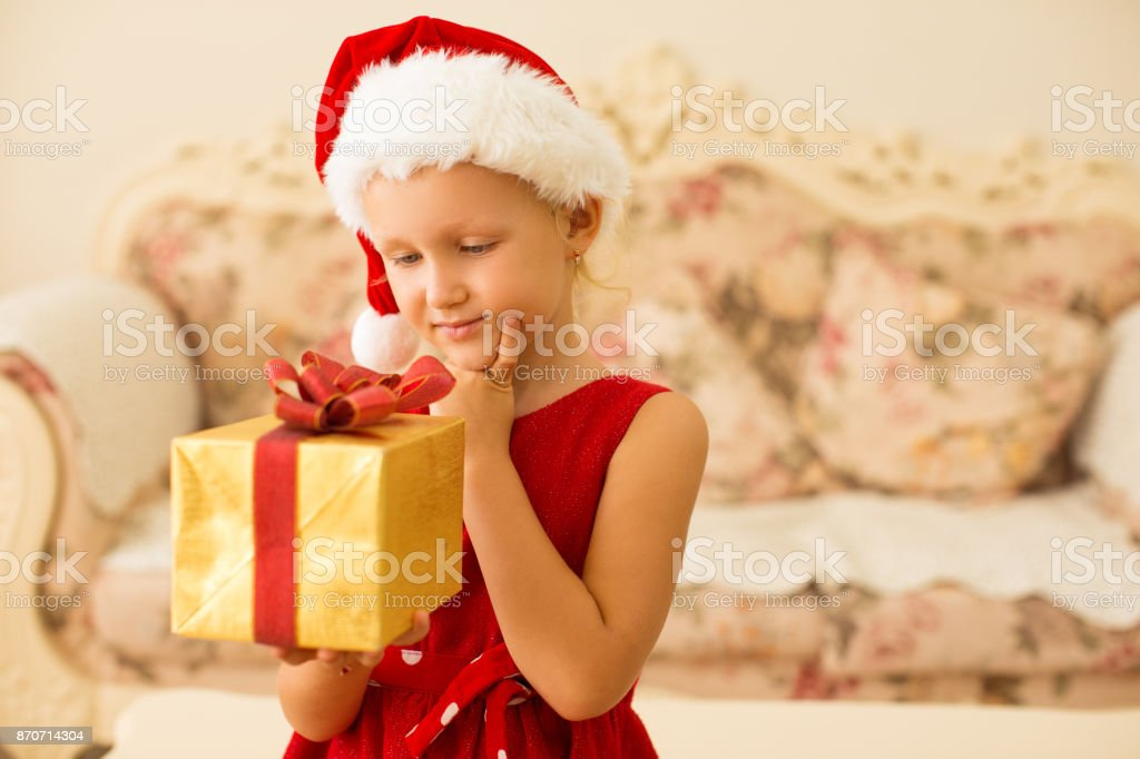 Pensive girl guessing what is in gift box. Smiling pretty kid holding...