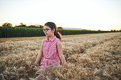 Curious and adorable 8 years old girl touching a wheat plant while exploring the beautiful nature