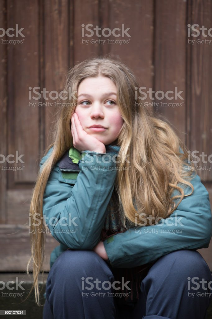 Young woman sitting outside looking away absorbed in her thoughts
