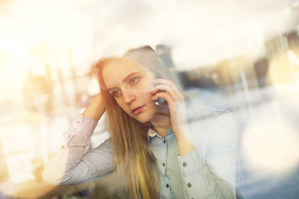 Pensive girl talking on phone about something in cafe – Foto
