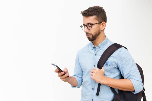 Nachdenklicher Kerl mit Rucksack mit Smartphone – Foto