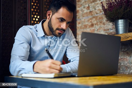istock Pensive handsome bearded male owner of trading company searching information about marketing agency noting their contacts to arrange formal meeting sitting in coworking space with laptop computer 904263506