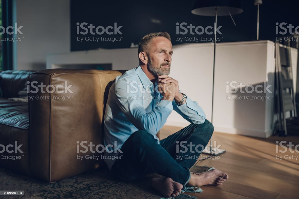 pensive handsome bearded midaged man sitting on floor stock photo