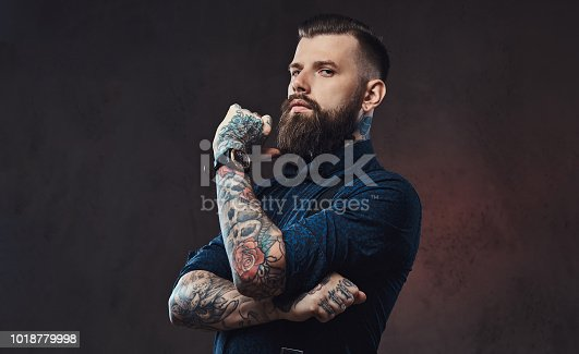 istock Pensive handsome old-fashioned hipster in a blue shirt and suspenders, standing with hand on chin in a studio. 1018779998
